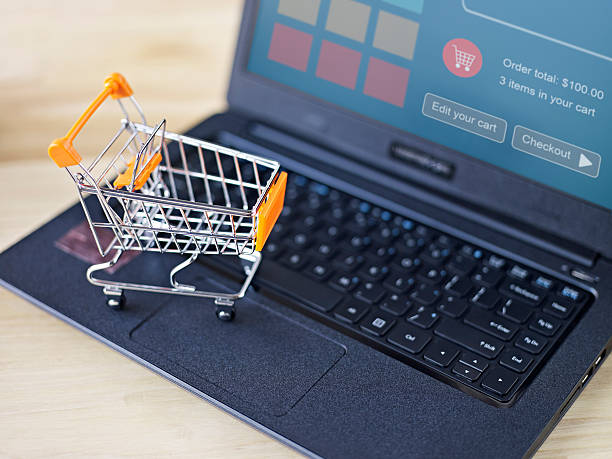toy shopping cart on top of a laptop computer for e-commerce concept.